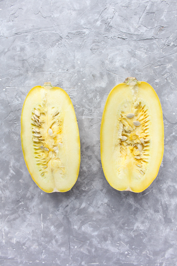 spaghetti squash cut in half with seeds inside.