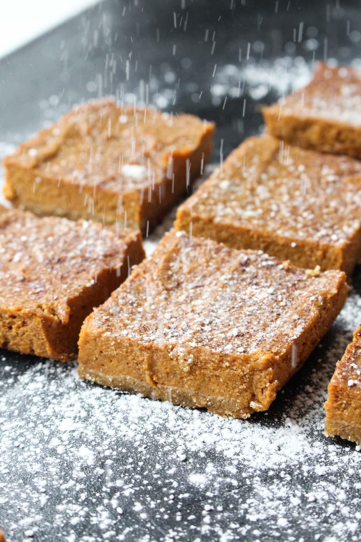 Paleo Pumpkin Pie Bars with powdered sugar falling on top.