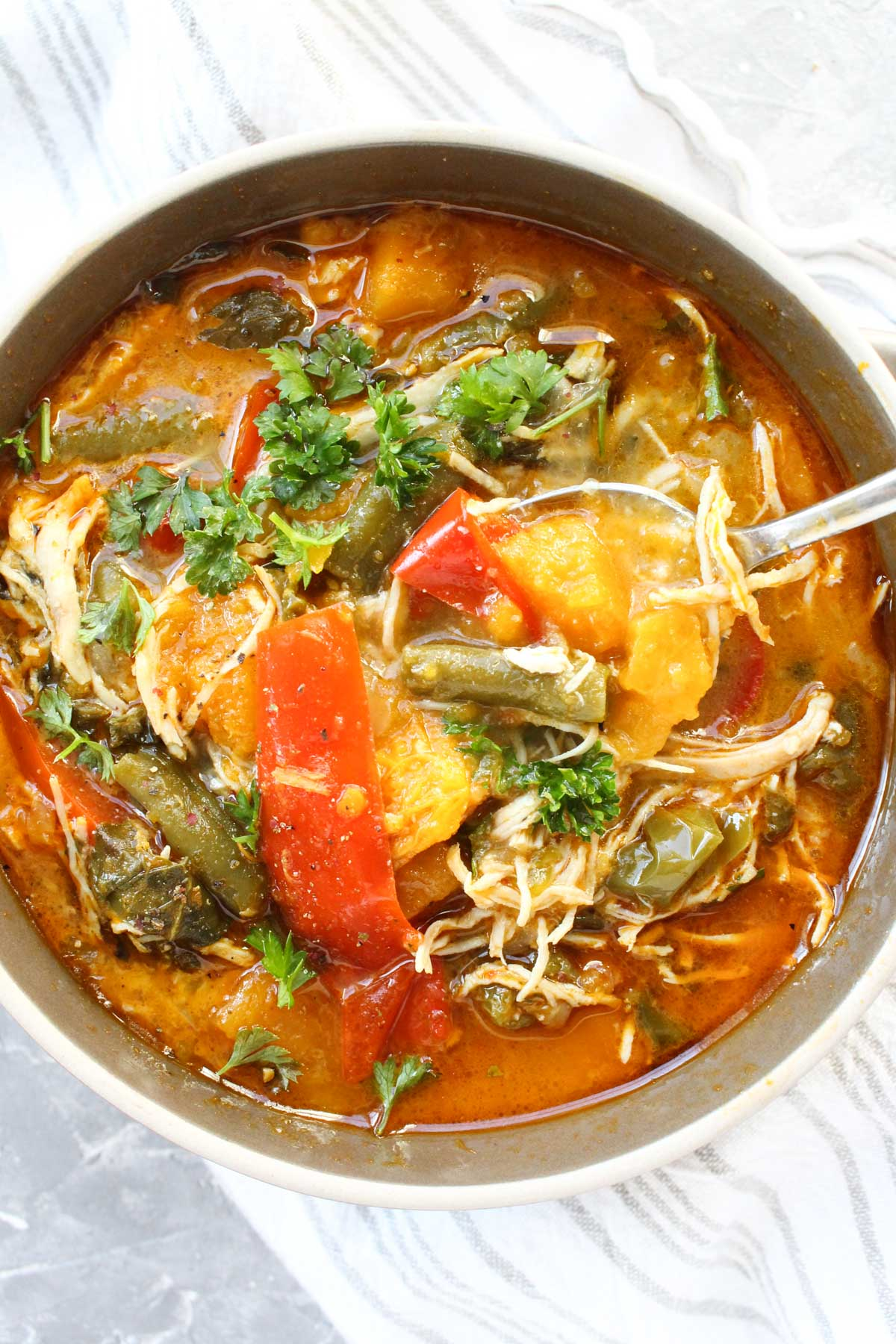 Bowl of red curry soup with spoon dipped inside.