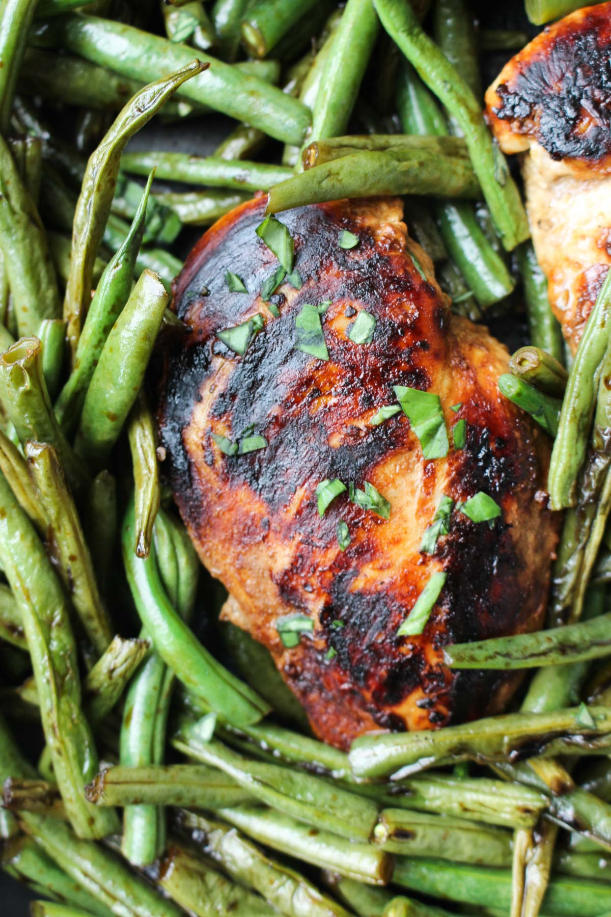 Close up shot of crispy balsamic chicken in the pan with fresh green beans.
