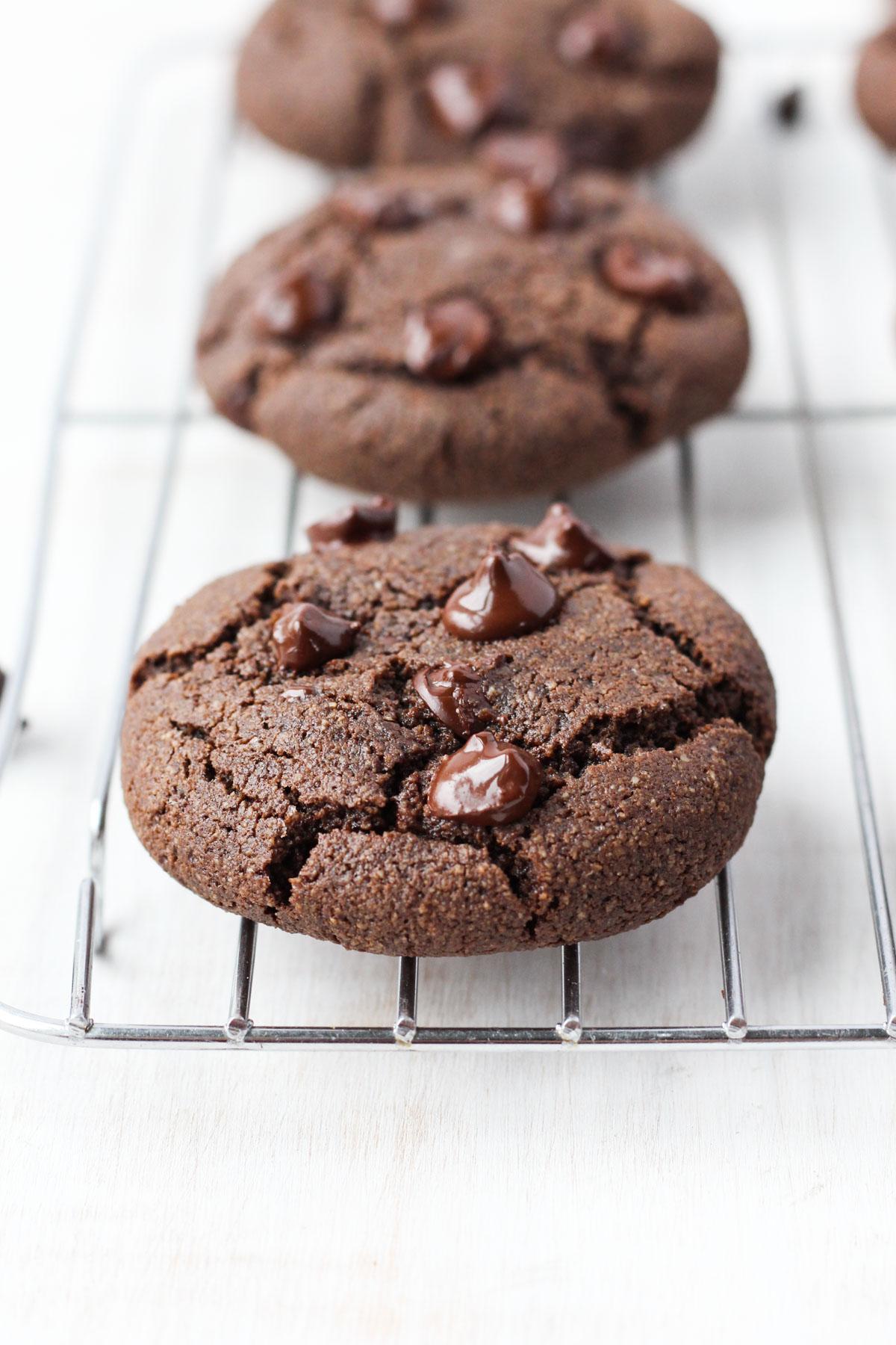 Chocolate cookies cooling on metal rack.