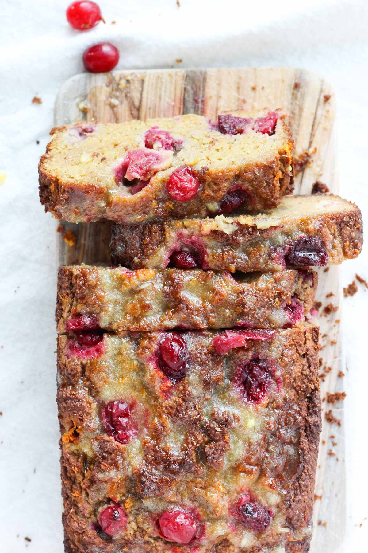 Overhead shot of cranberry orange bread on a wooden cutting board.