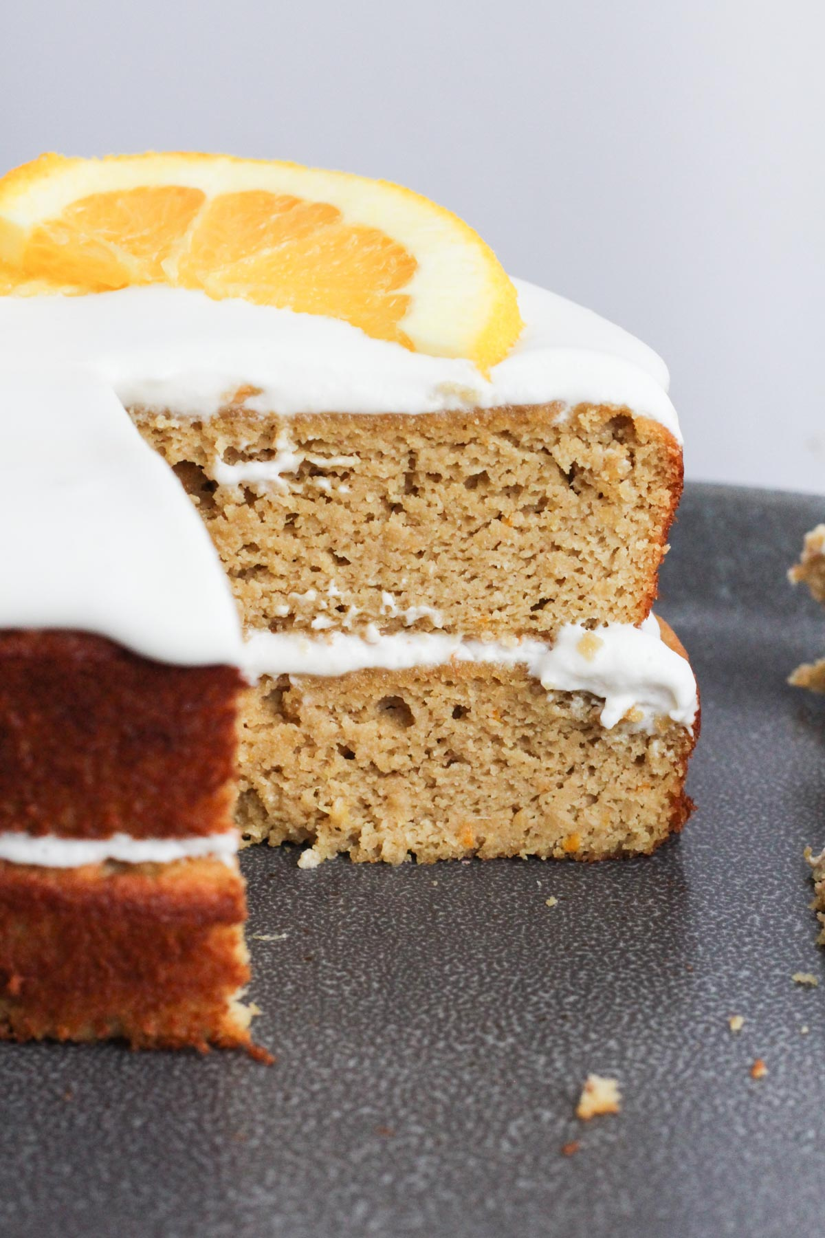 Gluten-free orange cake layered with coconut whipped cream and orange slices on top.
