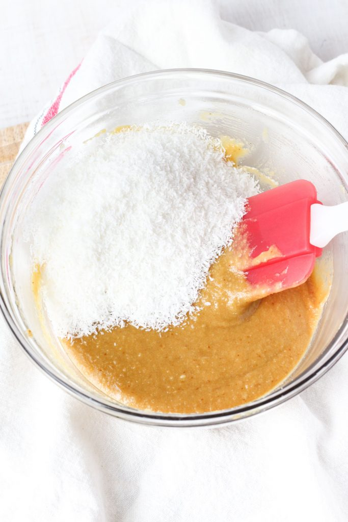 caramel and shredded coconut in a bowl with a spatula ready to fold them together.