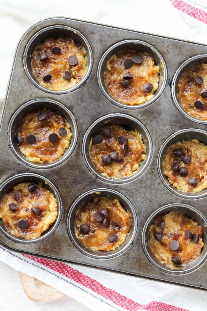 samoa muffins with the first layer of muffin, caramel, and chocolate chips.