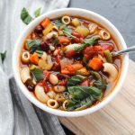 Big bowl of minestrone soup with fresh basil on top.
