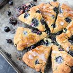 Pan of blueberry coconut scones with smashed blueberries around them, and a sweet drizzle on top!