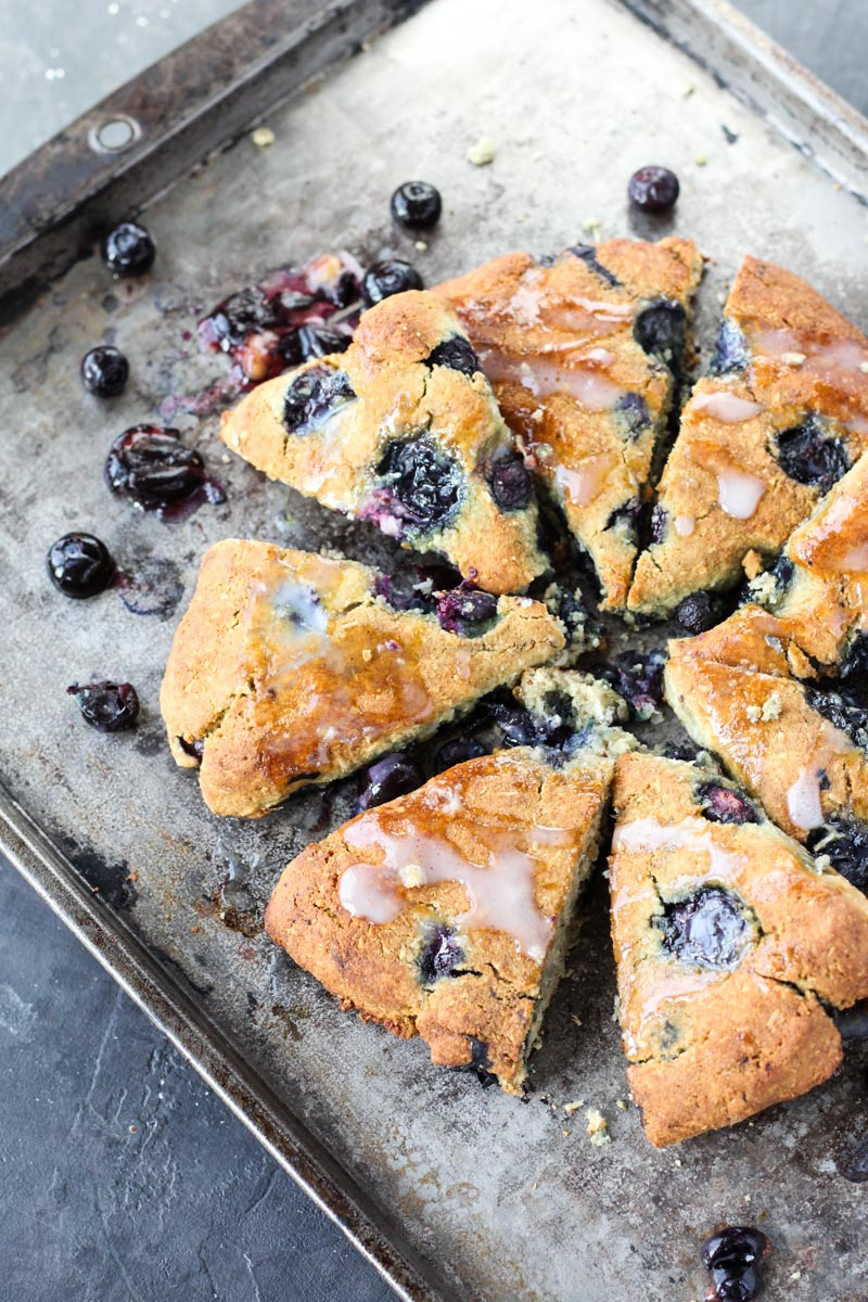 Baked scones lined up on a baking sheet.
