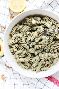 creamy walnut pesto in a large bowl with lemon slices around the outside.