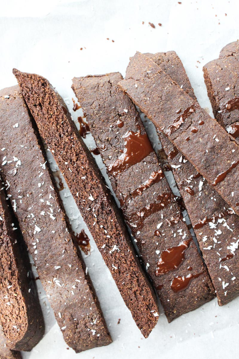 Gluten-free chocolate biscotti lined tilted on its side, and drizzled with melted chocolate.