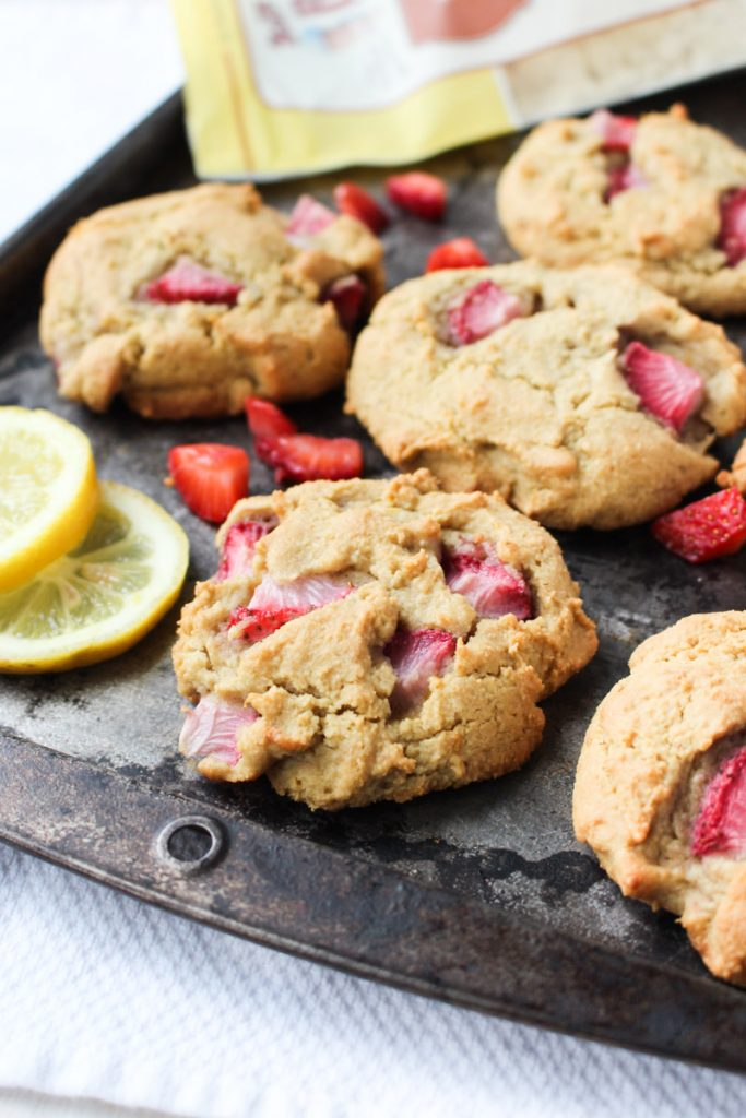Paleo Strawberry Biscuits cooling on baking tray with fresh lemons sliced on the side.
