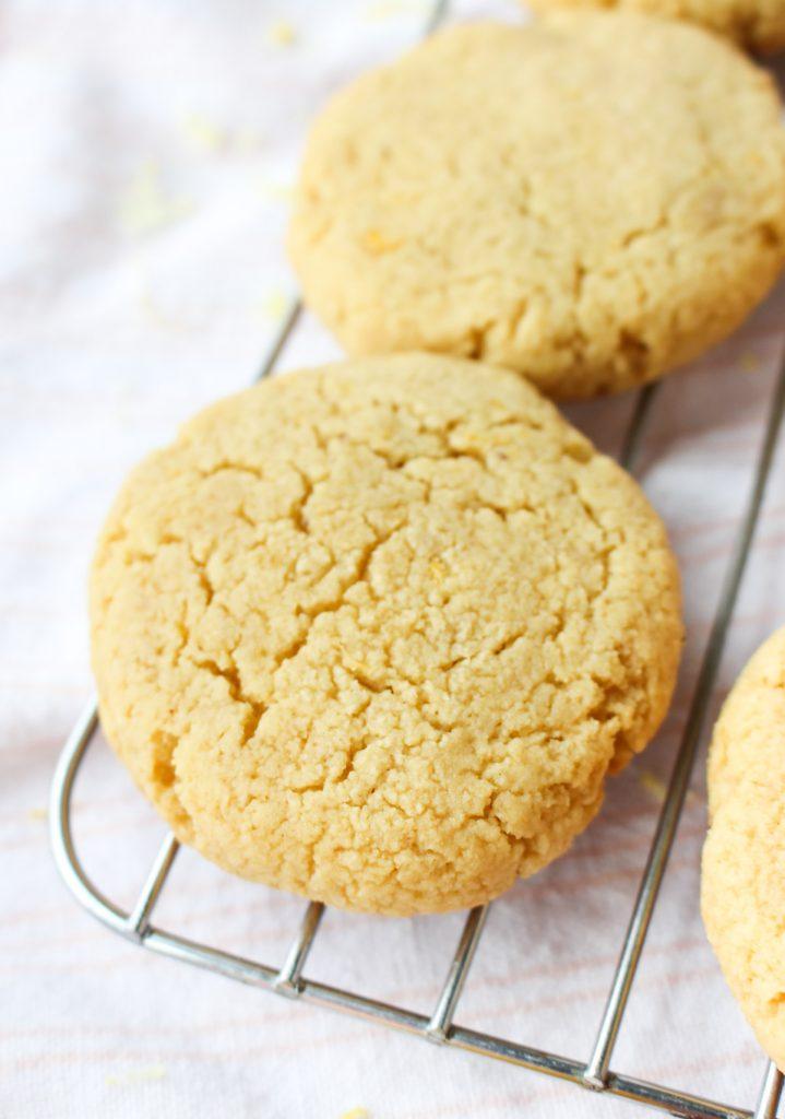 Soft paleo lemon cookies cooling on metal rack.