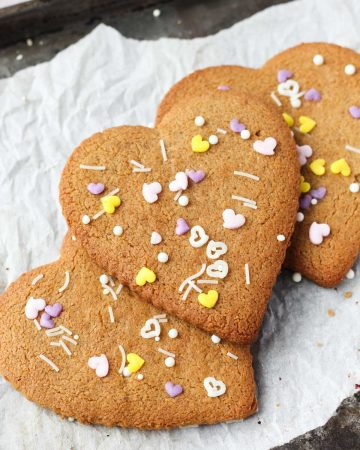 Heart shaped almond flour sugar cookies with sprinkles on top.