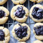 Overhead shot of lemon blueberry thumbprint cookies cooling on a metal rack.