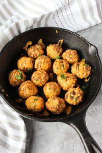Cauliflower meatballs in a skillet.