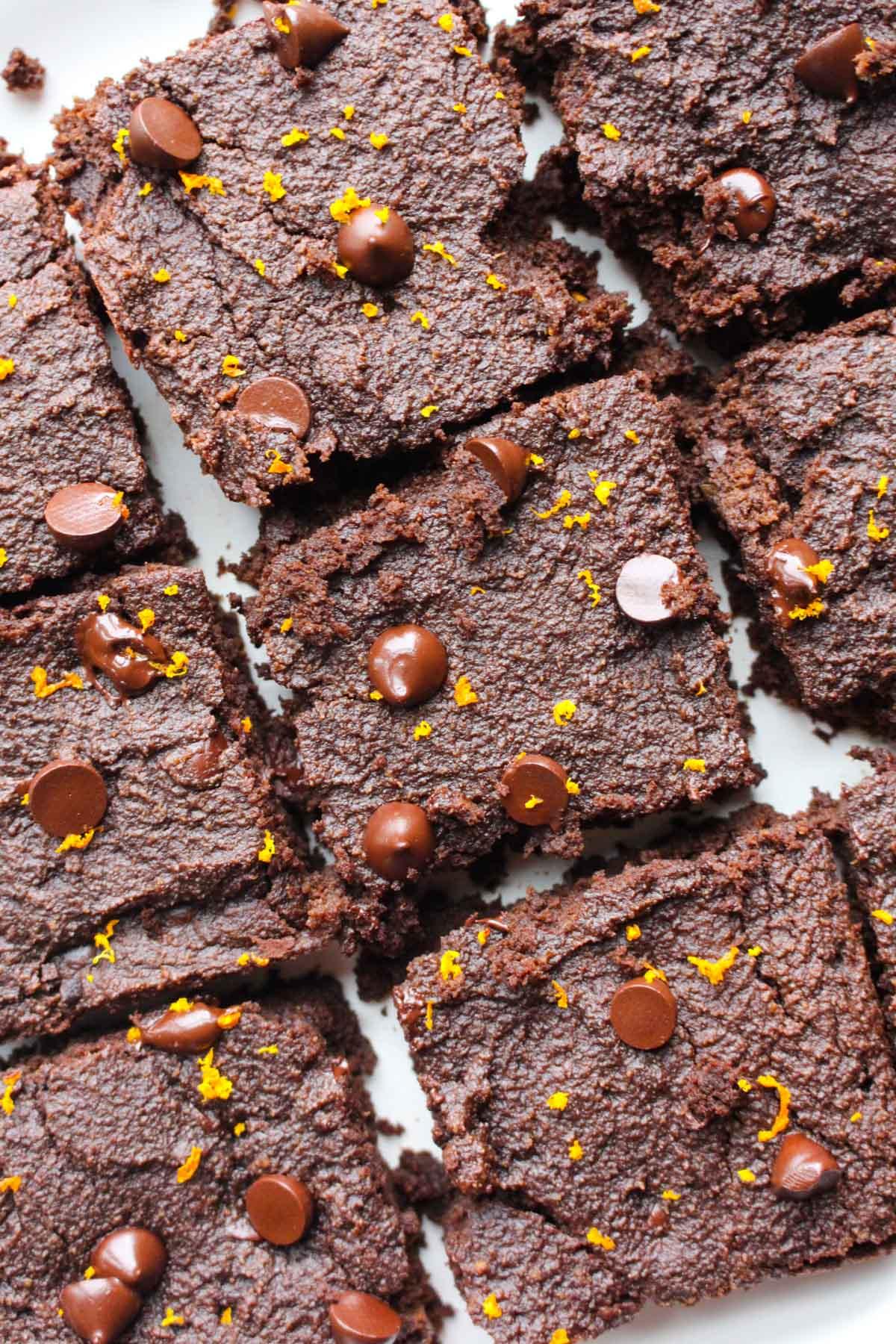 Overhead shot of brownies with orange zest on top.