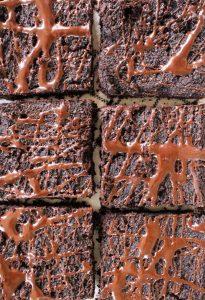 Overhead shot of fudgy vegan brownies with chocolate swirl on top.