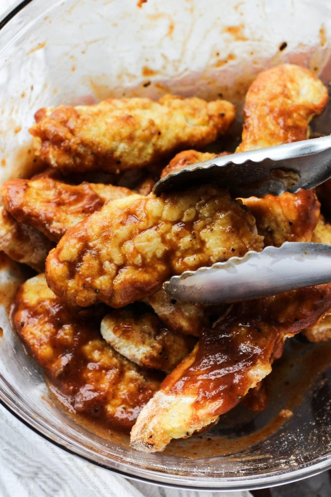 Chicken tenders being tossed in bbq sauce.