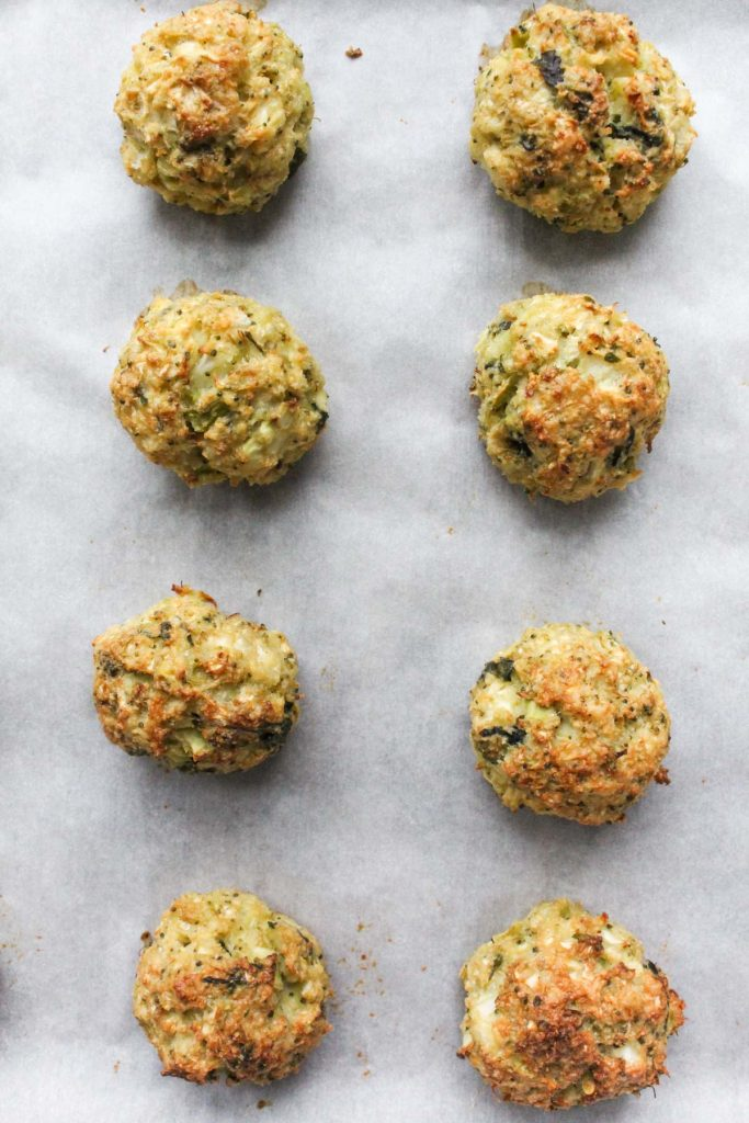Golden brown meatballs on baking sheet.