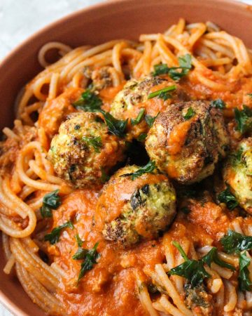 Close up shot of meatballs with sauce and spaghetti.