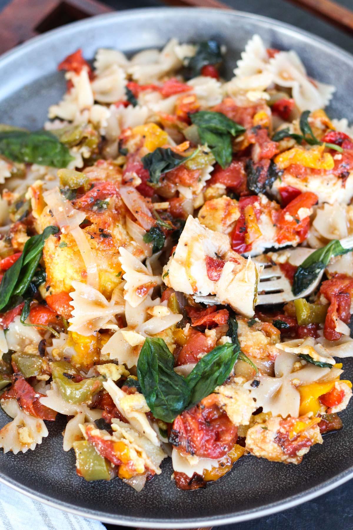 Plate of chicken cacciatore over gluten-free pasta.