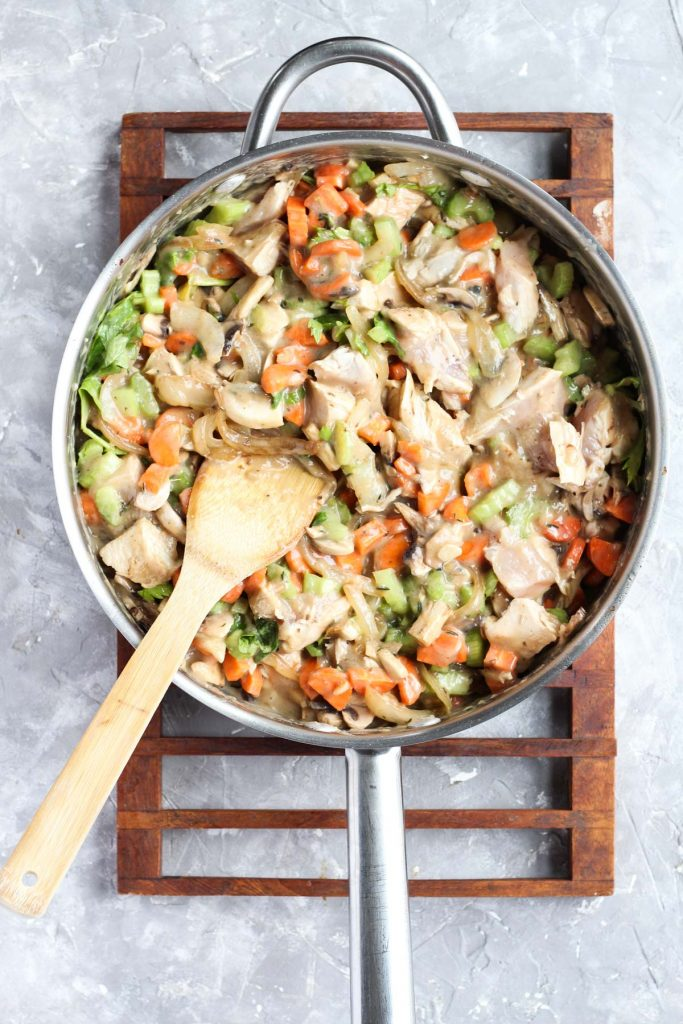 Vegetables and chopped chicken mixed together in the pan.