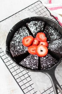 Overhead shot of cake slices in the skillet with powdered sugar and strawberries on top.