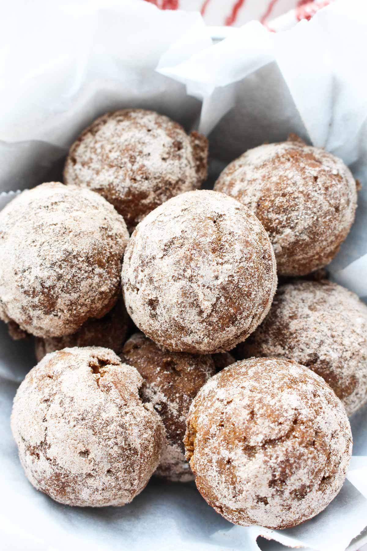 Donut holes in a parchment paper lined bowl.