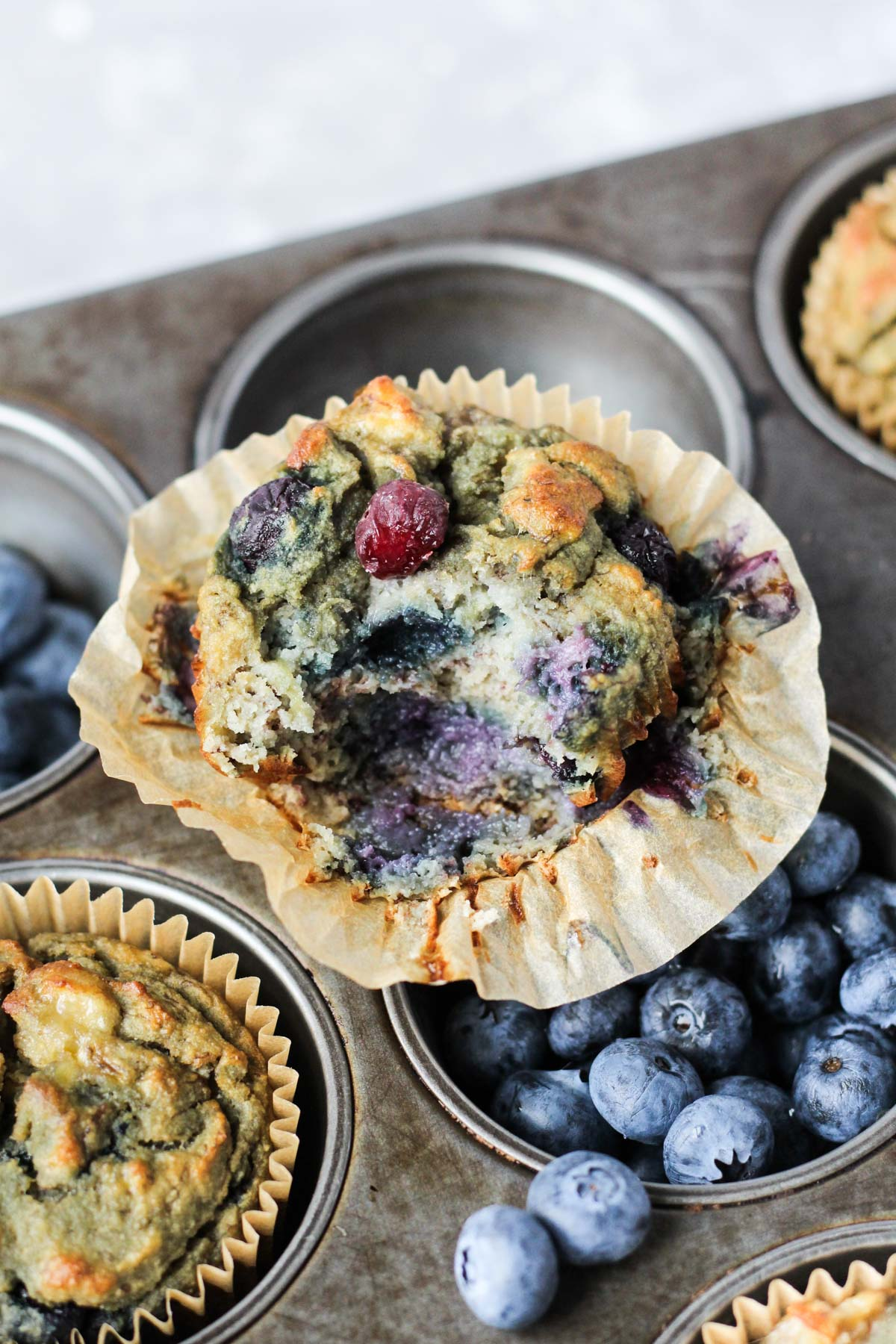 Close up shot of blueberry muffin with a bite taken out.