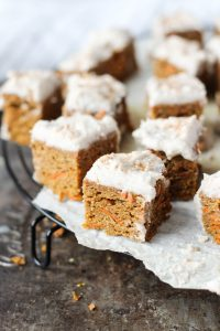 Mini carrot cake slices on parchment paper.