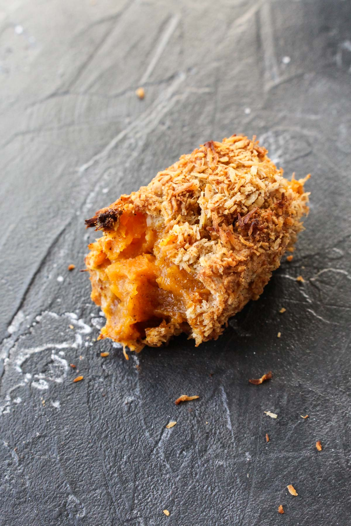 Close up shot of sweet potato tot with a bite taken out.