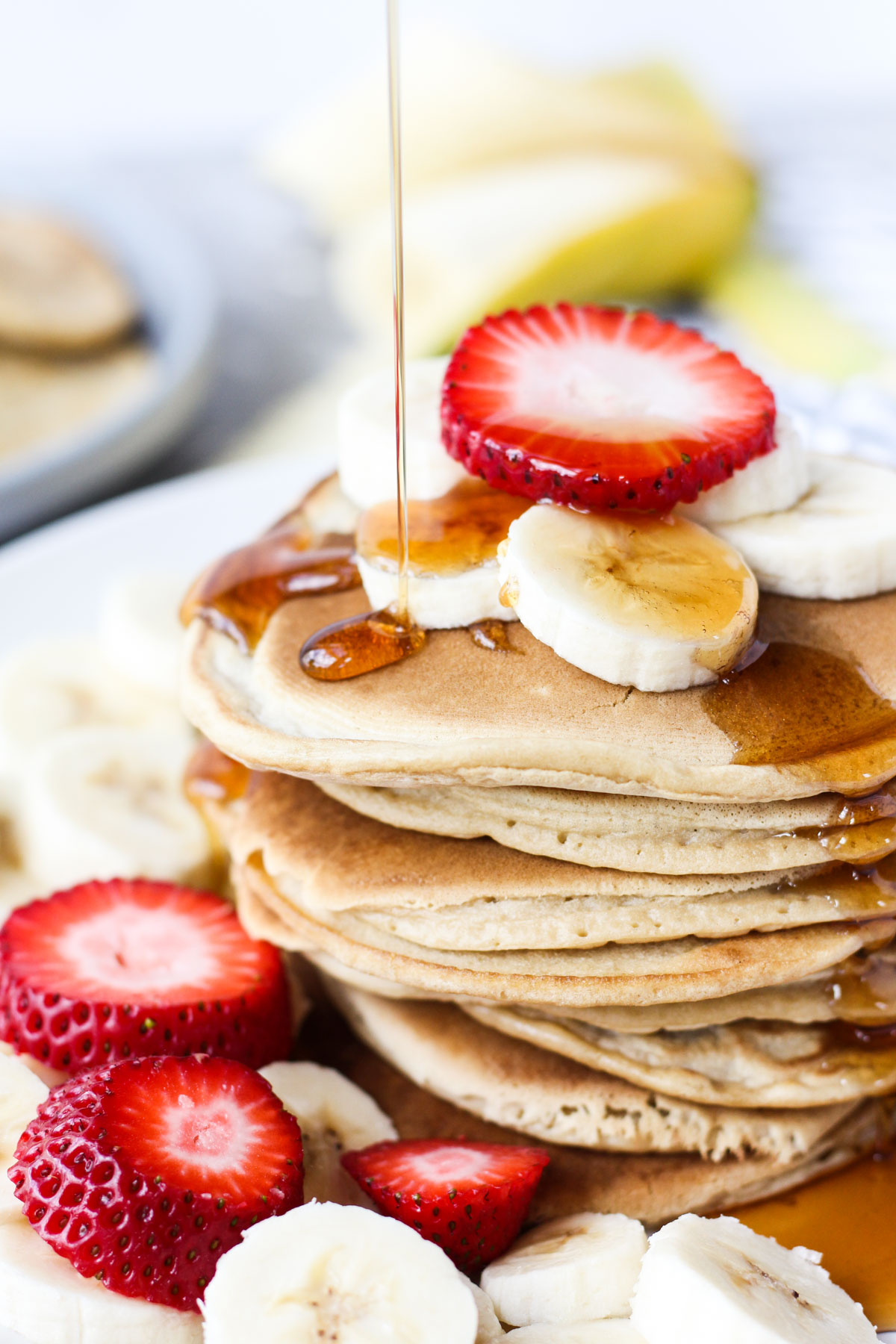 Pancakes stacked with maple syrup being poured on top.