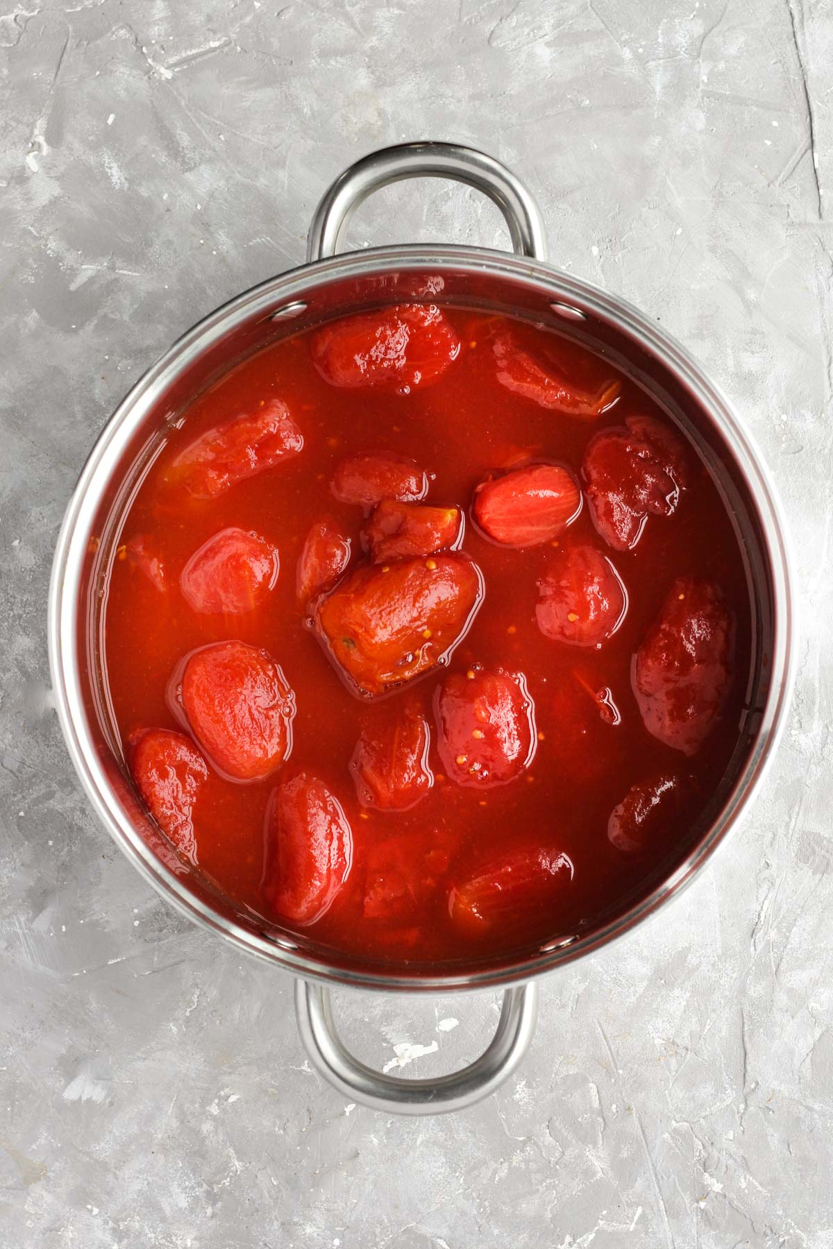 Whole peeled tomatoes in sauce pan.