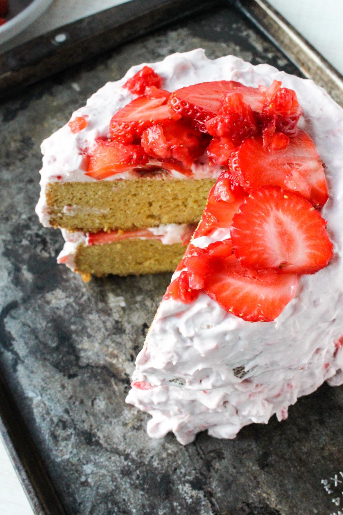 Overhead shot of gluten-free lemon cake with fresh strawberries on top.