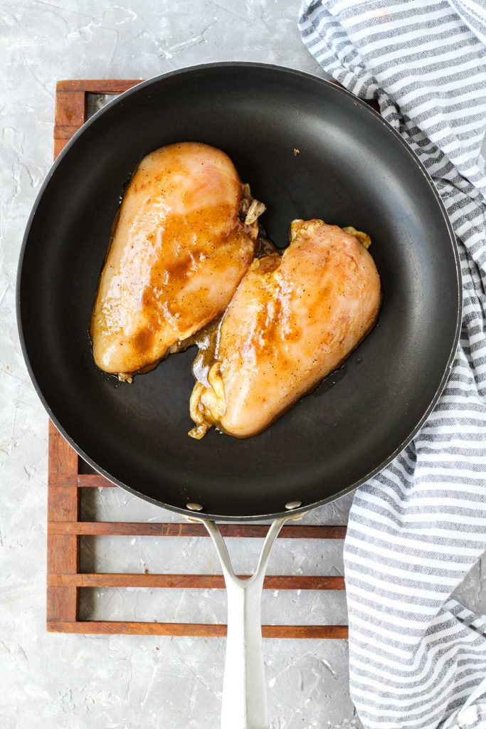 Chicken cooking on frying pan.