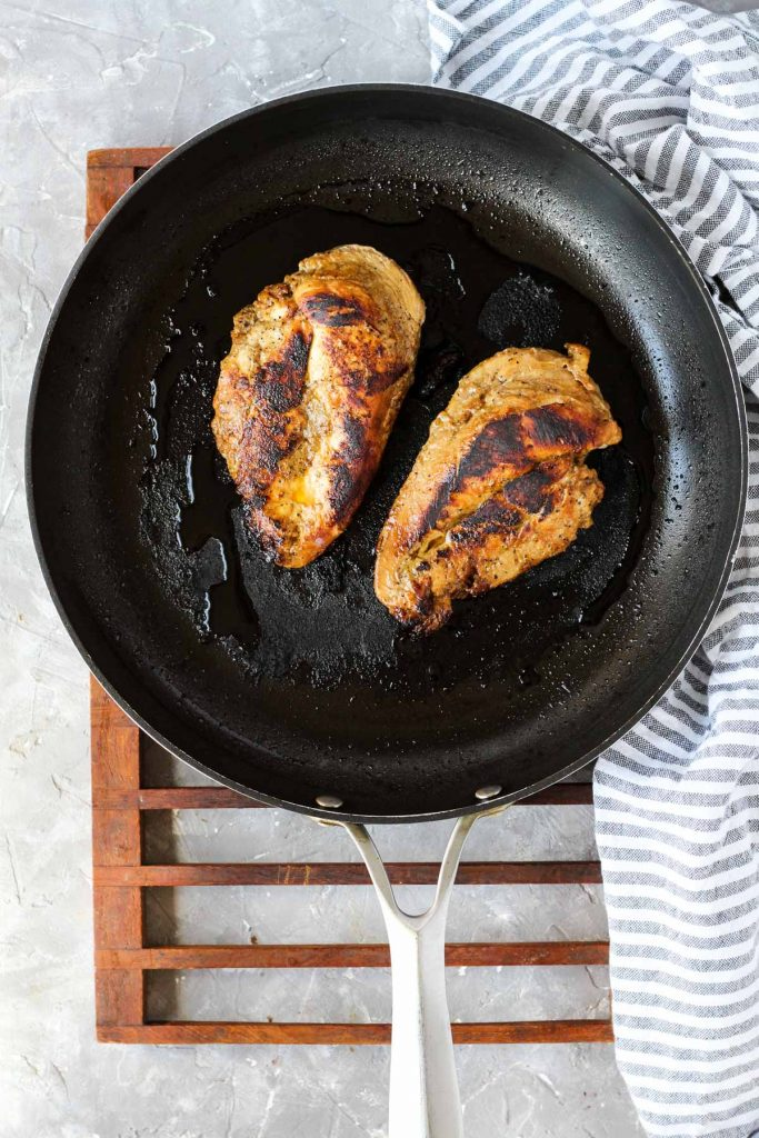 Chicken fully cooked on frying pan.