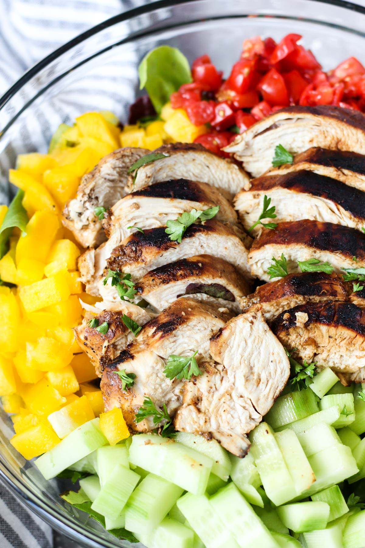 Side shot of balsamic chicken sliced on top of salad.