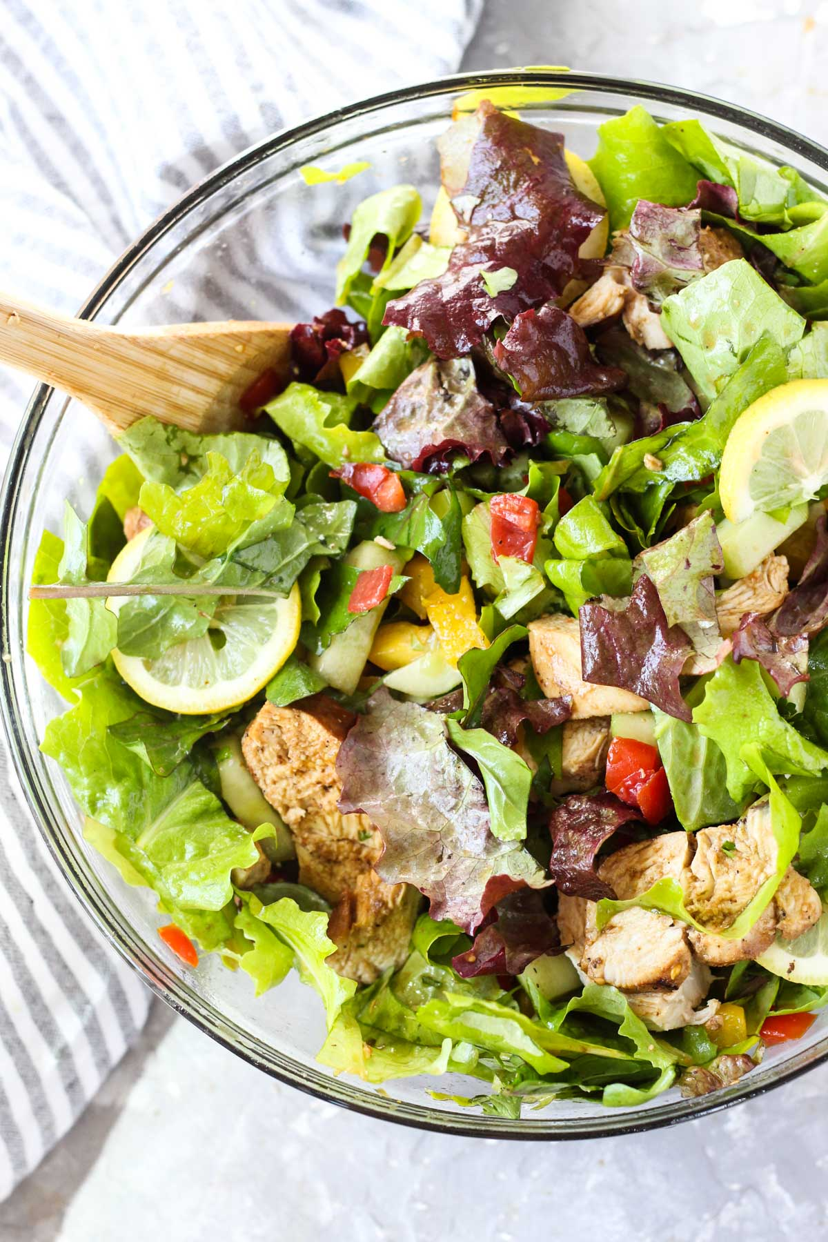 Salad tossed in large glass bowl.