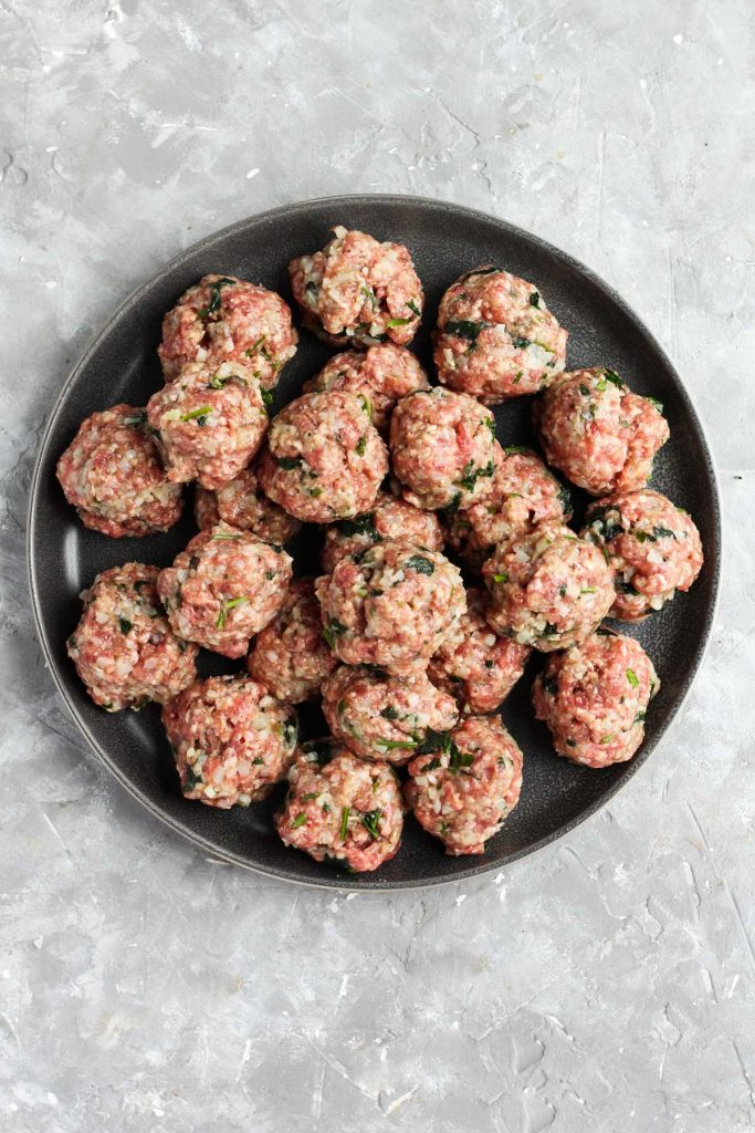 Raw meatballs on a plate.