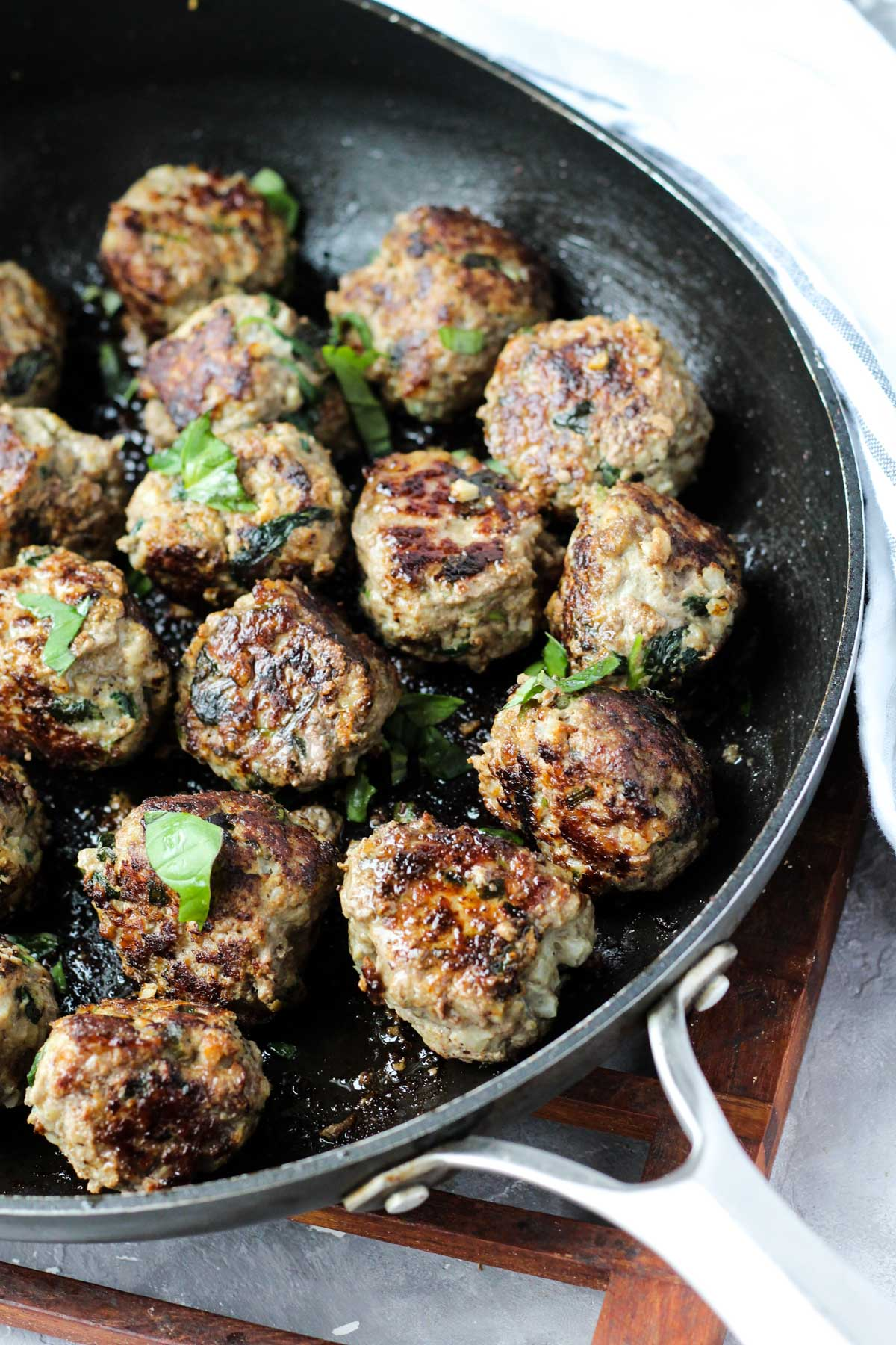 Skillet with sautéed meatballs.
