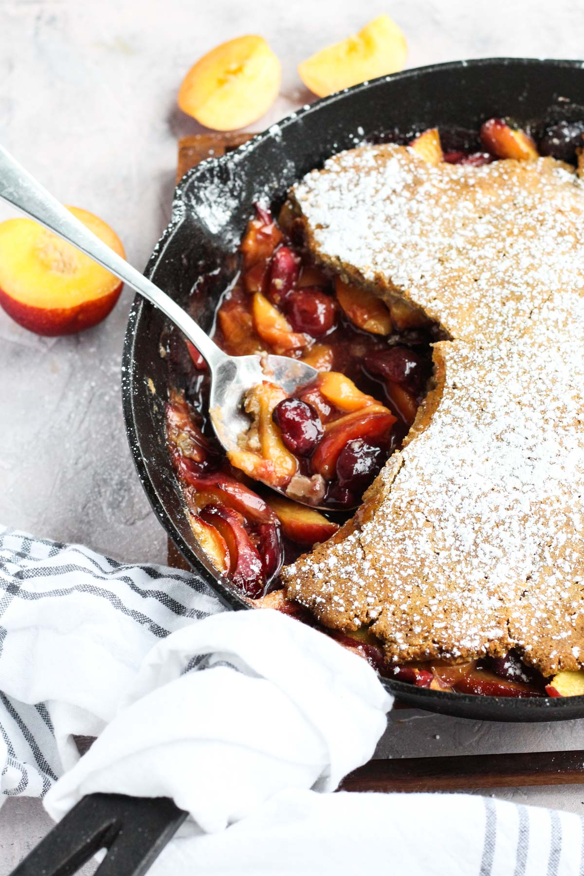 Side angle of cobbler with a spoon scooping out fruit.