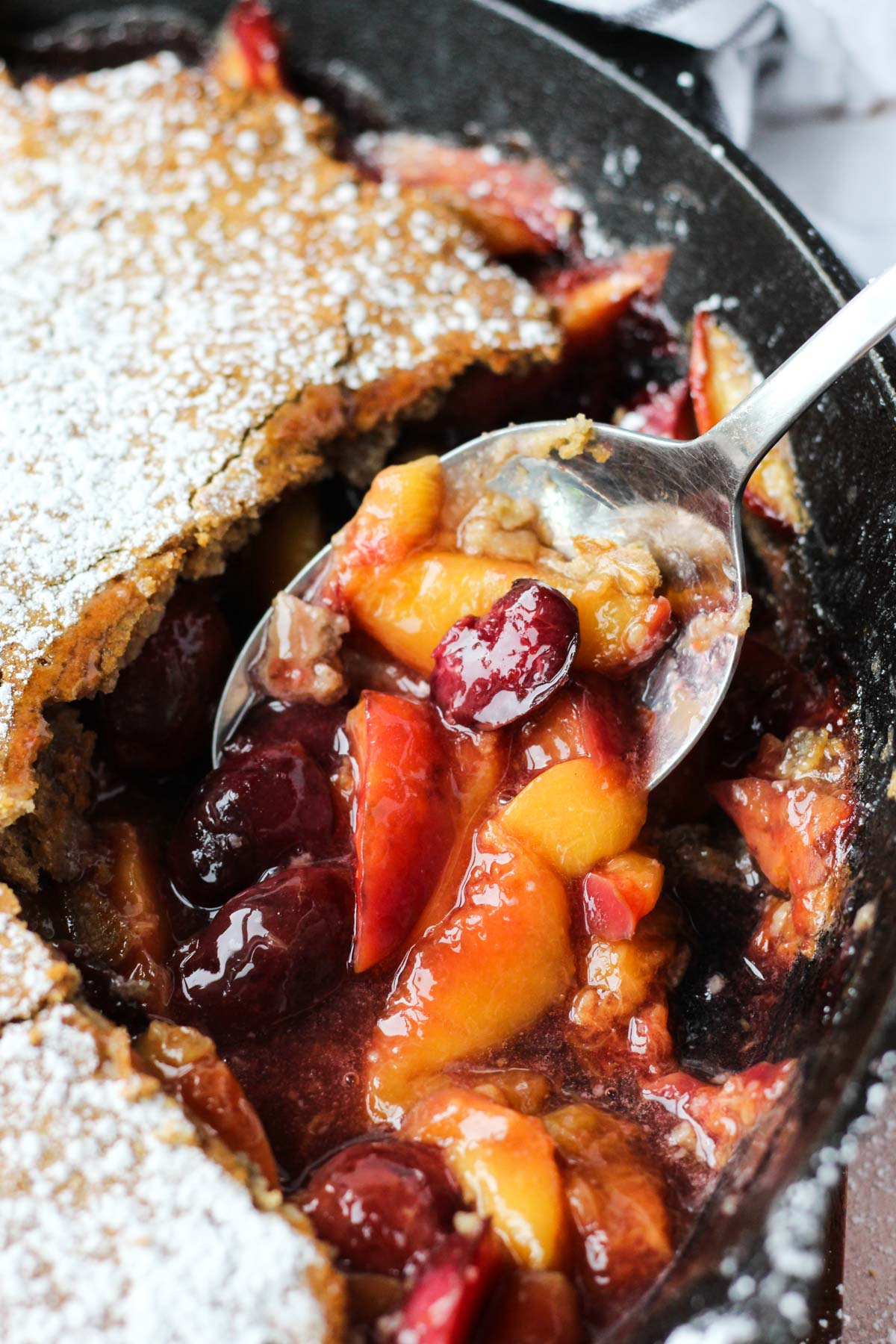 Spoon scooping out cobbler fruit.