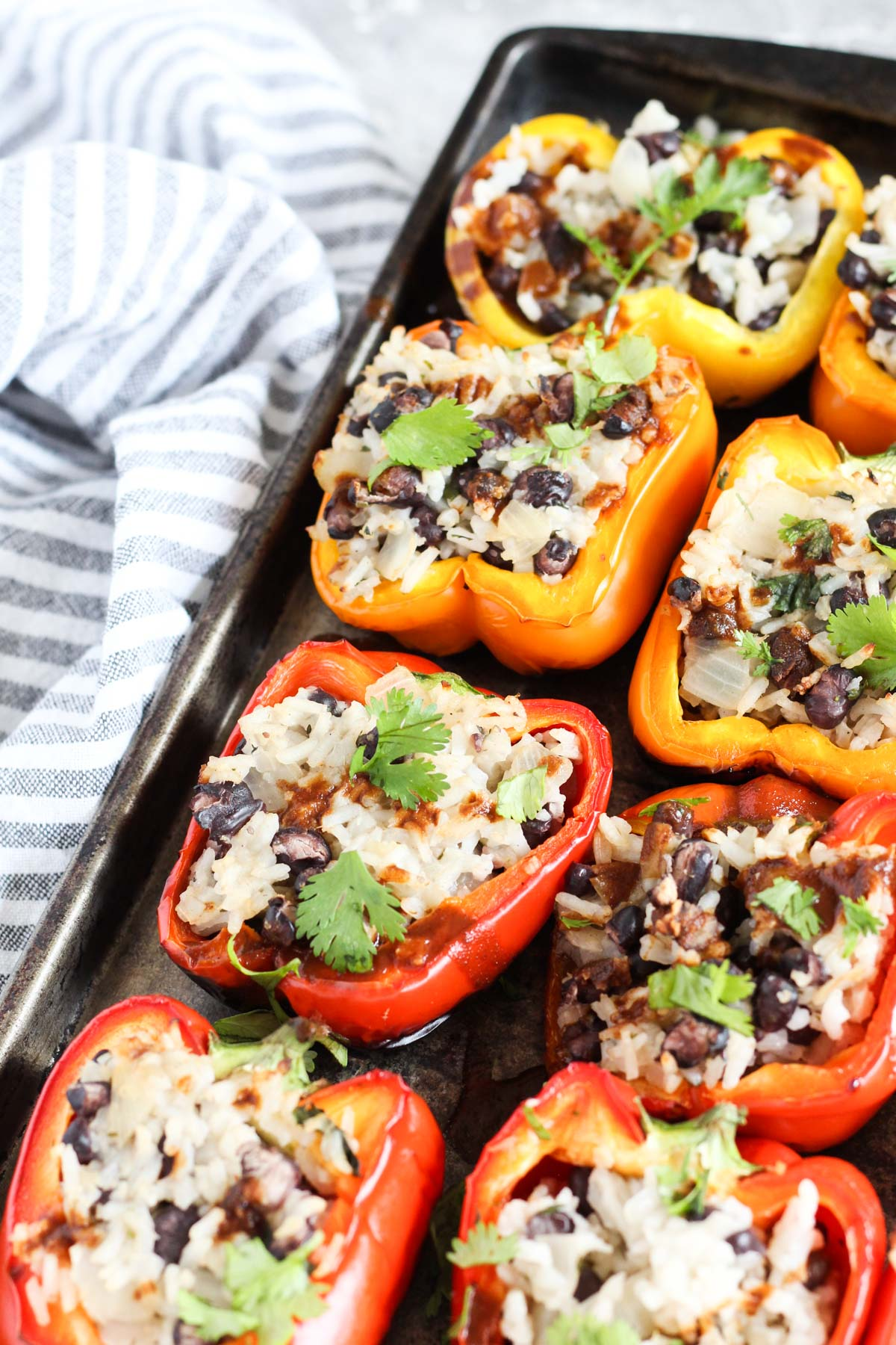 Grilled stuffed peppers lined up on a baking sheet.