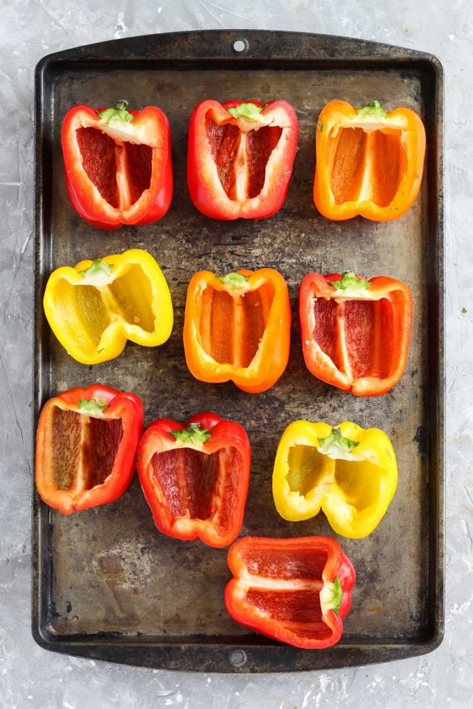 Peppers sliced in half on baking sheet.