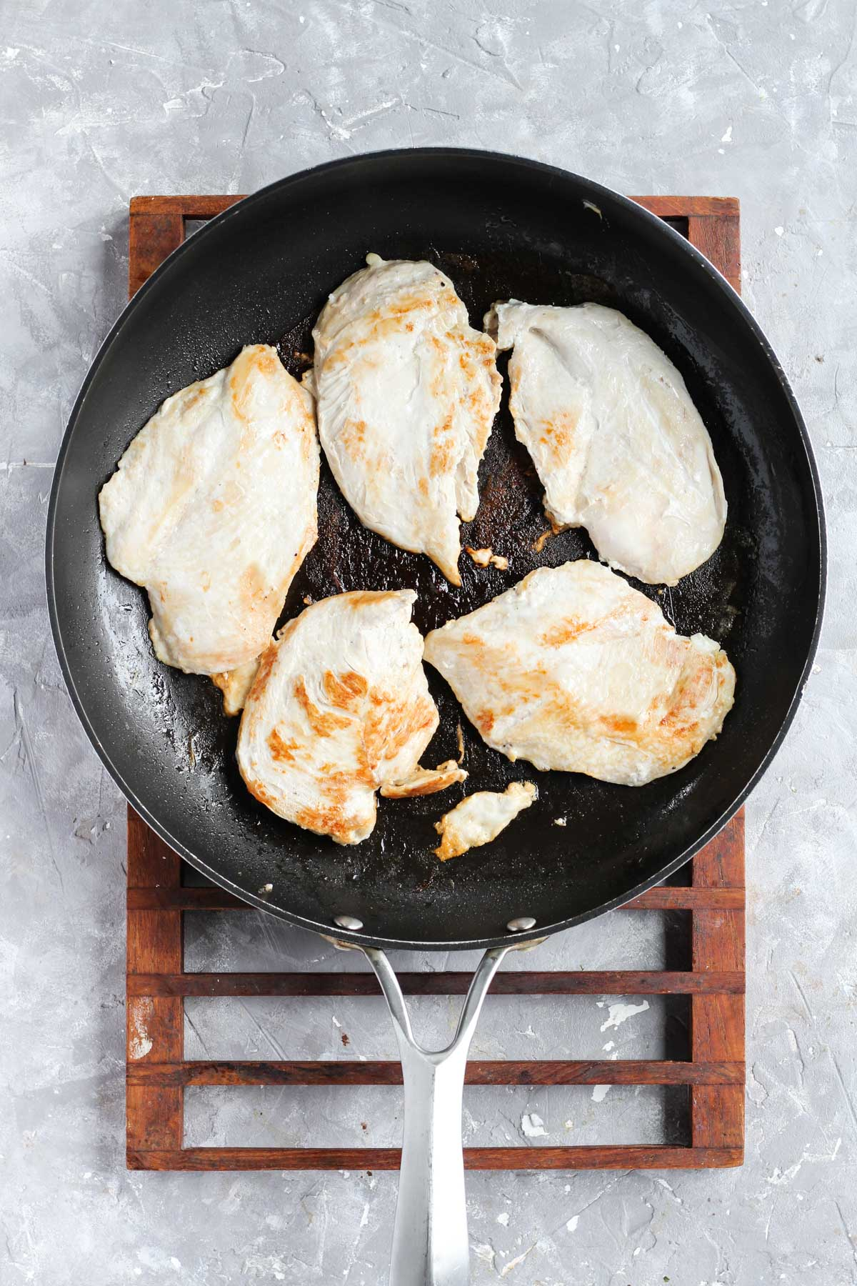 Cooked chicken in frying pan.