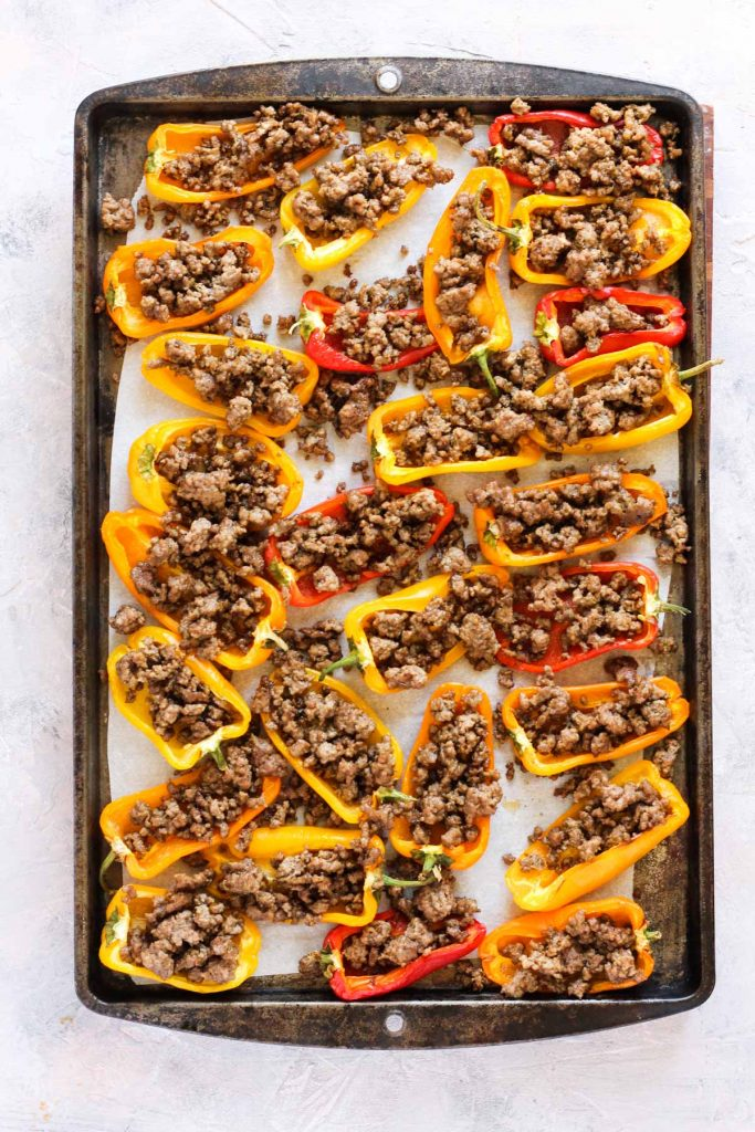 Peppers stuffed with meat on baking sheet.