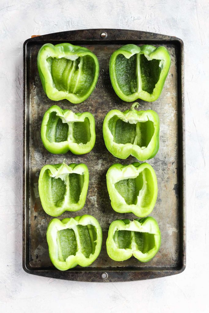 Bell peppers sliced in half and prepped on a baking sheet.