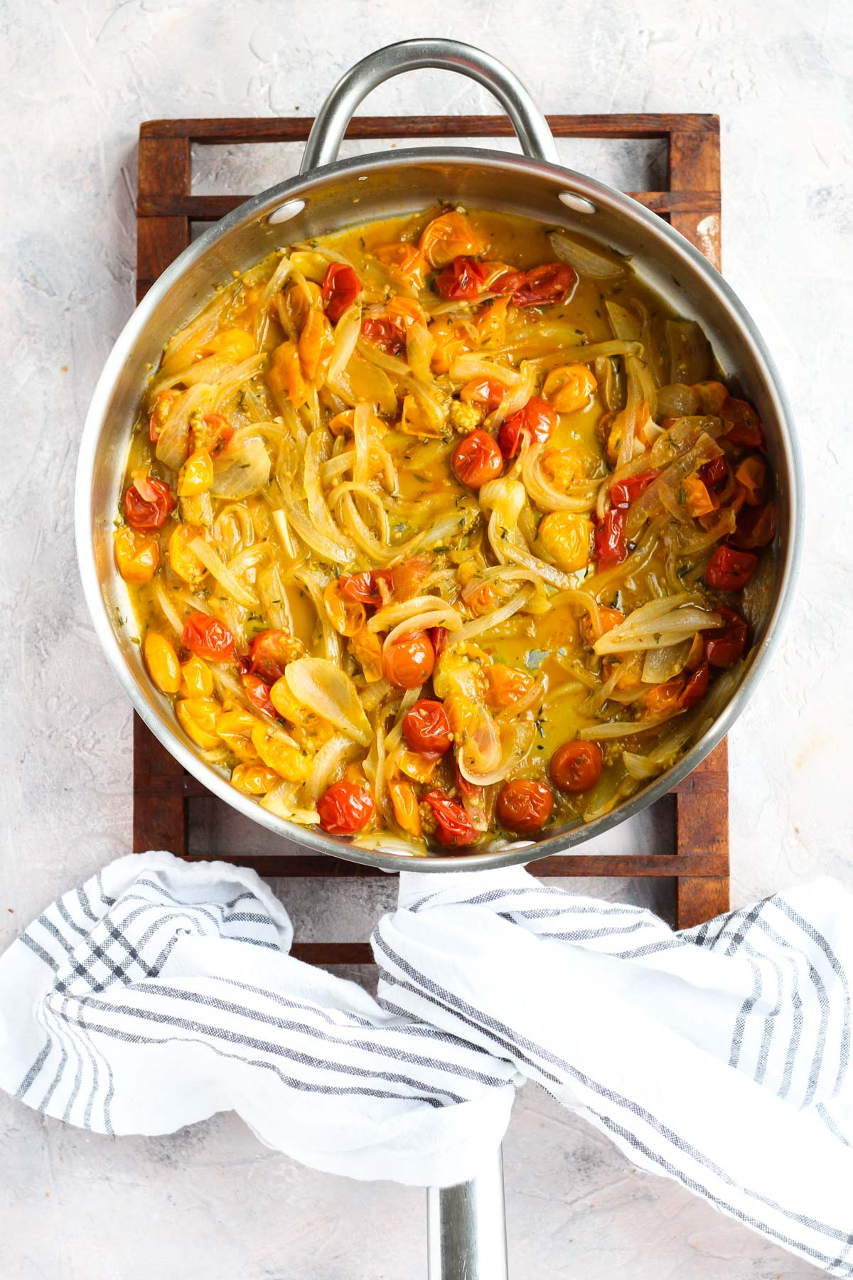 Caramelized onions with cherry tomatoes and herbs cooking in a pan.