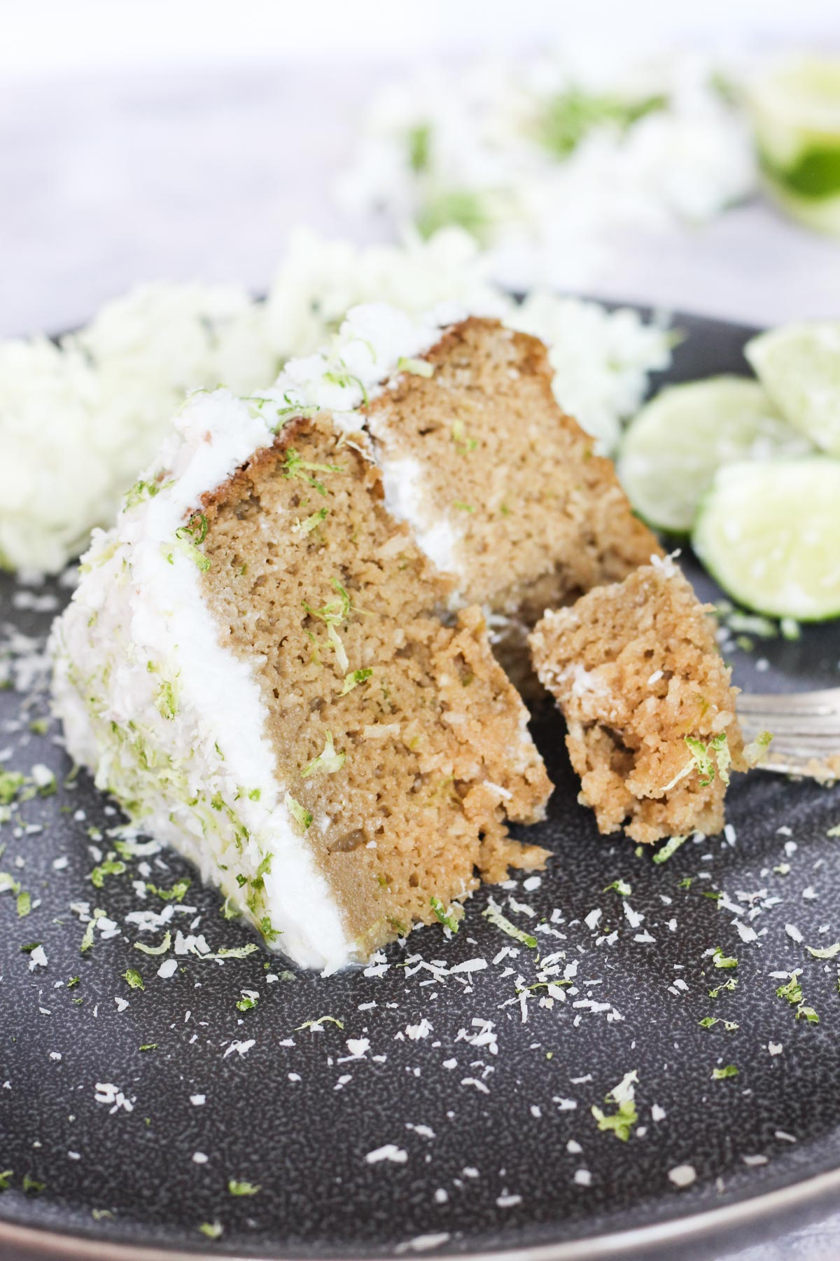 Slice of coconut lime cake on a grey plate.