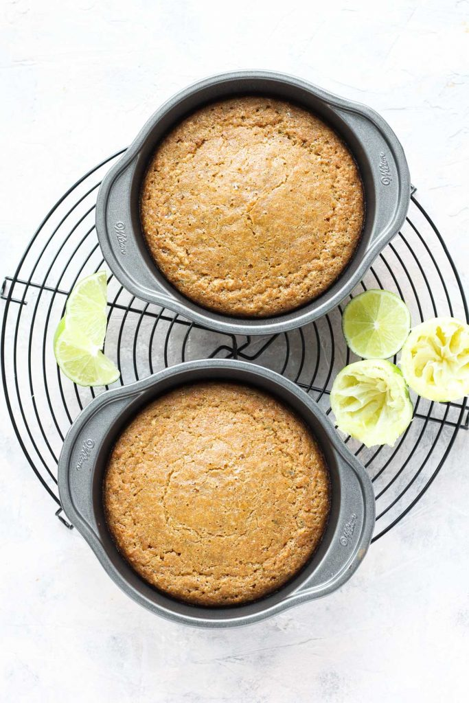 Two small cakes cooling on metal rack.